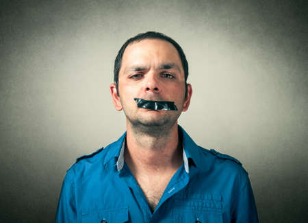 silenced: portrait of man with the taped mouth