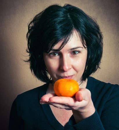 Brunette girl holding a tangerine near her mouth