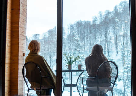 Family with snowdrops and drink mugs on balcony, Winter time