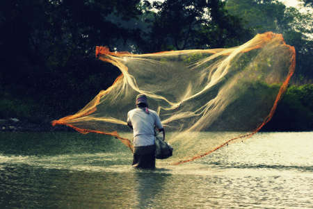 fishingnet: a local person fishing in a pond at North Guwahati in Assam, India
