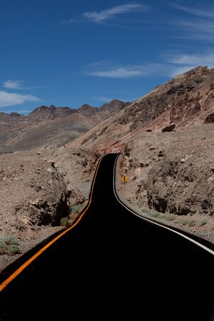 Suggestive winding road leading somewhere in the desert of Death Valley National Park, a soft ribbon among the arid rocks of the desert Banque d'images