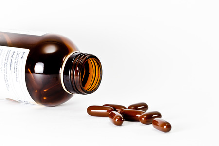 reliever: Brown Pills pouring out of the brown bottle on white background