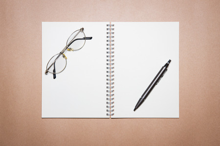 Glasses, notebook, and pen on a brown paper. View from above.