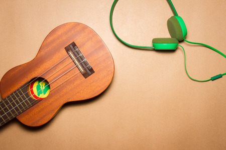 Green headphones and ukulele on a brown paper background
