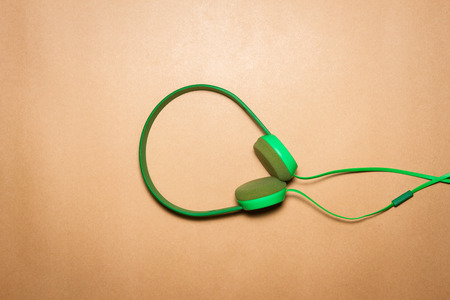 Green headphones on a brown paper background