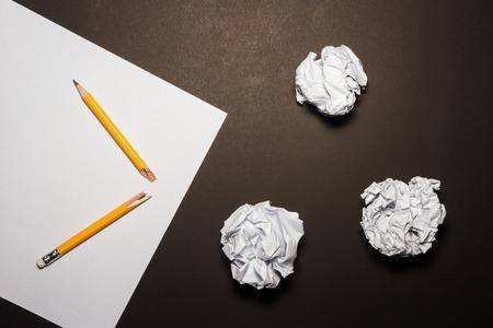 lapiz y papel: Lápiz quebrado, papel, papel arrugado en el fondo negro. Frustraciones Negocios, estrés en el trabajo y el concepto de examen fallado. Disparo a arriba. Foto de archivo