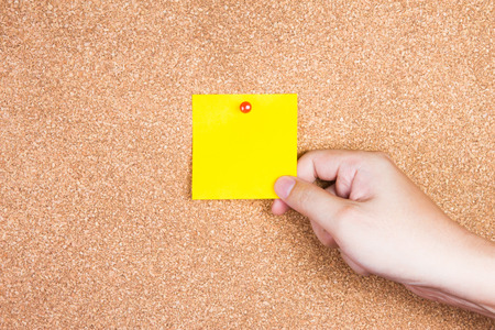 note board: yellow reminder sticky note on cork board with hand holding, empty space for text
