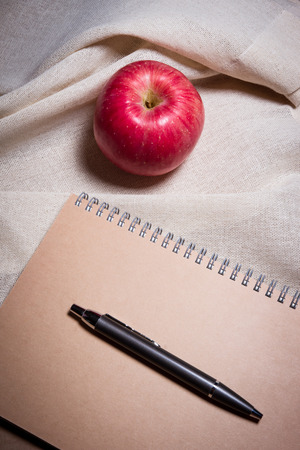 apple pen and notebook on white cream color fabric