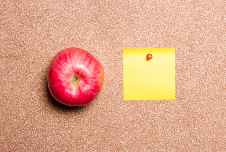 apple and yellow reminder sticky note on cork board, empty space for text 版權商用圖片