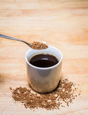 Cup of coffee and spoon of Coffee Granules on wooden table.