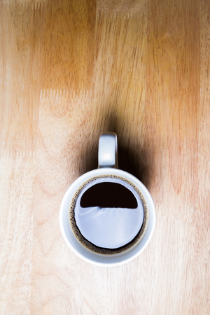 Cup of coffee on wooden table. Shot at above