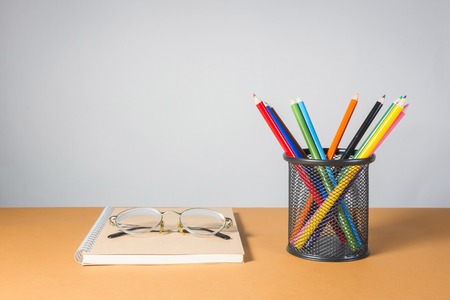 A stack of color pencils and glasses on notebook