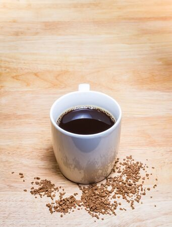 Cup of coffee and Coffee Granules on wooden table.