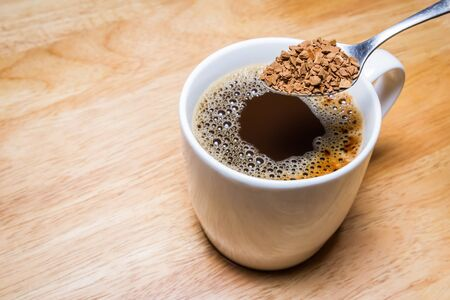 Cup of coffee and spoon of Coffee Granules on wooden table. focus on Granules.