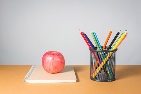 an apple on a notebook and A stack of color pencils
