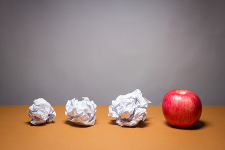 an apple and crumpled paper. Business frustrations, Job stress and Failed exam concept. 版權商用圖片
