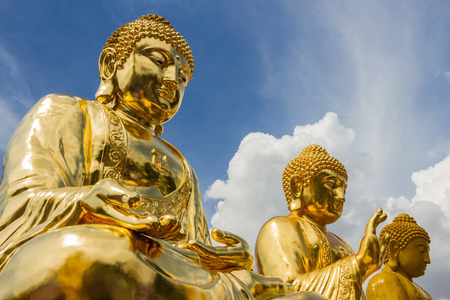 Three giant gold buddha statues. Shot at Wat Trimitr Vityaram Voravihahn Temple of the Golden Buddha, Bangkok, Thailand.