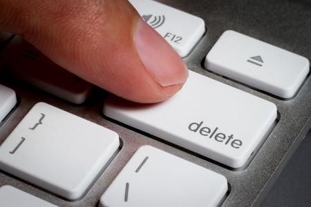 Closeup of finger on delete key in a keyboard.