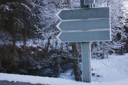 Three arrow signs pointing to the left in a winter landscape. Stock Photo