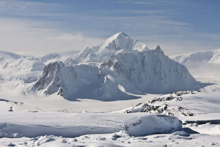 mountain peak is covered with white snow in Antarctica photo