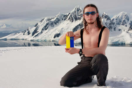 Man on top of the mountain holding a white form. Antarctica. photo