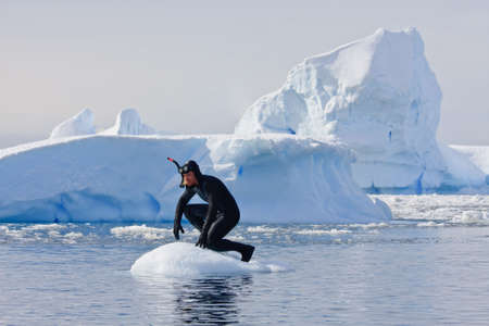 A diver on the ice against the blue iceberg. Antarctica