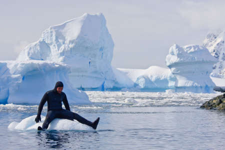 Diver on the ice against the blue iceberg. Antarctica Stock Photo - 6302703