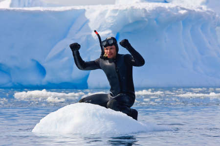 Diver on the ice against the blue iceberg. Antarctica Stock Photo