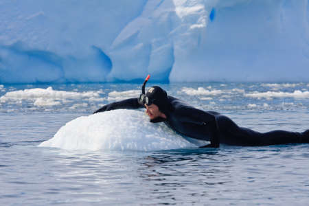 Diver on the ice against the blue iceberg. Antarctica Stock Photo - 6302700