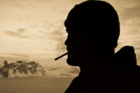 Silhouette of male smokers in the background of the mountains of Antarctica photo
