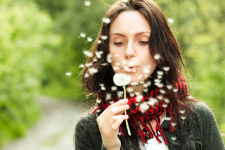 Girl blowing on white dandelion in the forest Stock Photo - 6792076