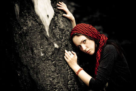 Girl in a red kerchief hugs charred wood photo