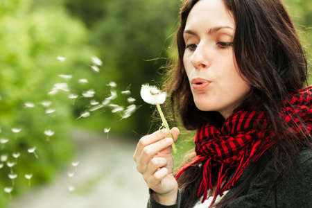 Girl blowing on white dandelion in the forest Stock Photo - 6792078