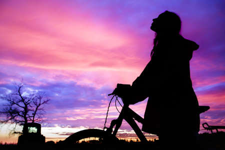 Girl with a bicycle watching the sunset photo