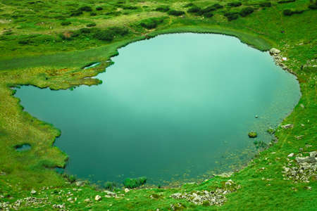 Alpine lake in a green valley photo