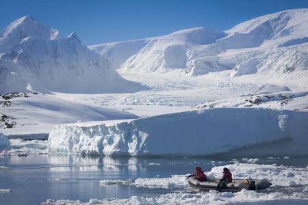 boat near the snowy glaciers in Antarctica photo