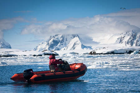 man in the red boat in Antarctic waters photo