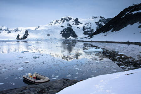 boat in Antarctic waters, mountains on the background photo