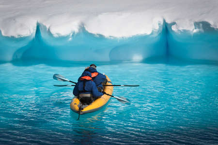 Two men in a canoe among icebergs in Antarctica photo
