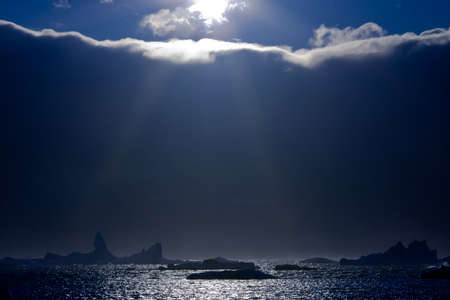 dramatic sky: The sun peeps out from the edge of the clouds. On the horizon are visible icebergs Stock Photo