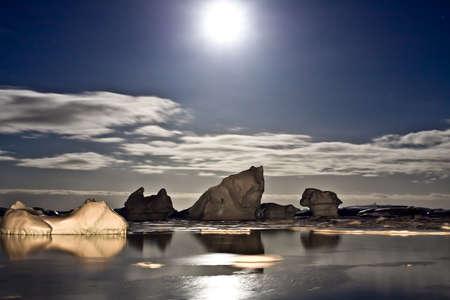 Summer night in Antarctica.Icebergs floating in the moonlight photo