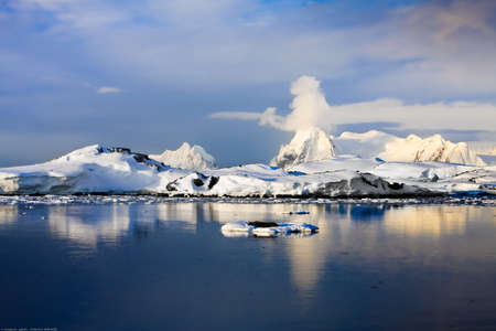 arctic landscape: The mountains and their reflection in the water with ice. The clouds in the sky. Stock Photo
