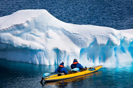 Two men in a canoe among icebergs in Antarctica Stock Photo - 8765495