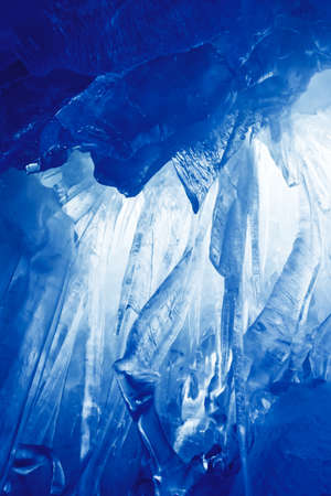 blue ice cave covered with snow and flooded with light photo