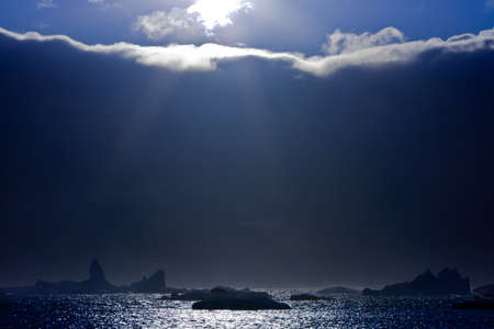 The sun peeps out from the edge of the clouds. On the horizon are visible icebergs photo