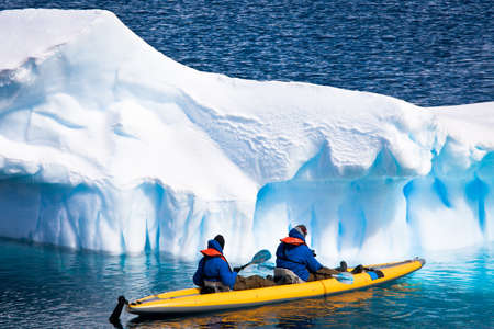 Two men in a canoe among icebergs in Antarctica Stock Photo