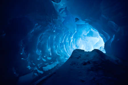 cavern: blue ice cave covered with snow and flooded with light Stock Photo