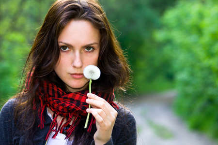 Girl holding in her hand a white dandelion photo