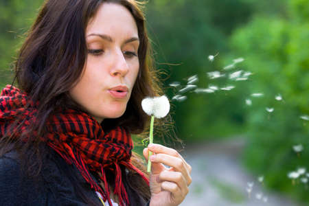Girl blowing on white dandelion in the forest photo