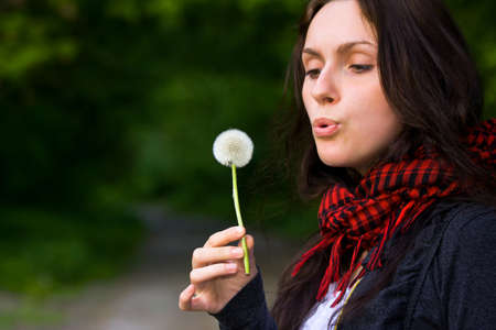 Girl blowing on white dandelion in the forest Stock Photo - 8986862